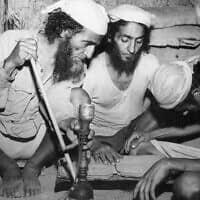 שלושה יהודים קוראים בתורה במחנה הפליטים היהודי בחשיד, בקולוניה הבריטית דאז עדן, תימן, מרץ 1949 (צילום: סוכנות הידיעות האמריקאית/ג'רלד מלמד)