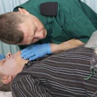 פרמדיק מבצע פעולות החיאה בחולה שהתמוטט (צילום: iStock Henfaes)