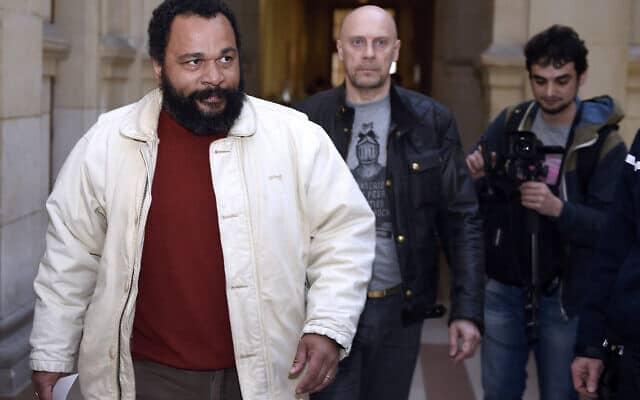 דיידונה מ'באלה מ'באלה, משמאל, ואלן סורל, מגיעים לבית המשפט בפאריז לקראת משפטו של סורל באשמת הסתה לשנאת יהודים, 12 במרץ 2015 (צילום: Loic Venance/AFP דרך Getty Images)