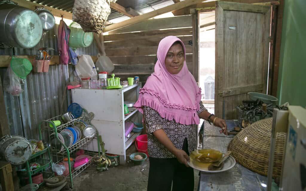 אישה מבשלת במטבח הקהילתי במחנה העקורים בפאלו, אינדונזיה. הגישה המוגבלת לשירותי רפואה והמגורים בדיור ארעי וצפוף מעמידים את הקהילה שלה בסיכון גבוה לחלות בקוביד-19 (צילום: אליסון ג'ויס/AJWS)