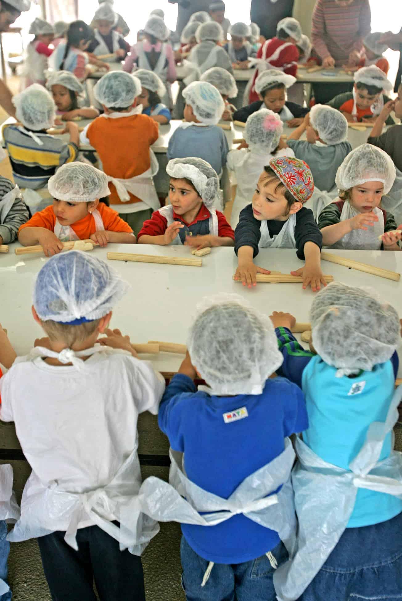 ילדי ההתנחלות נווה דקלים בגוף קטיף מכינים מצות לפסח, ארכיון, 2005 (צילום: AP Photo/Baz Ratner)