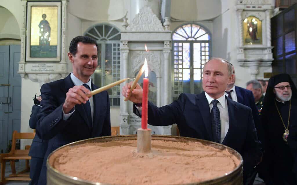 ולדימיר פוטין ובשאר אל אסד מדליקים נר בכנסיה האורתודוקסית בדמשק, בעת ביקורו של נשיא רוסיה שם, ב-7 בינואר 2020 (צילום: Alexei Druzhinin, Sputnik, Kremlin Pool Photo via AP)