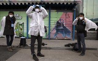 עיתונאים מתמגנים לפני סיור במפעל סיני, בשיא משבר הקורונה שם (צילום: AP Photo/Ng Han Guan)