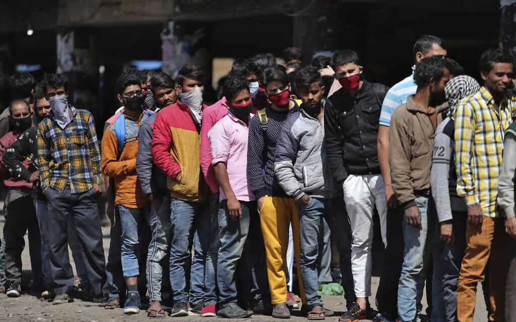 עובדים הודים שנתקעו הרחק מביתם עומדים בתור וממתינים לחלוקת אוכל, ב-22 במרץ 2020 (צילום: AP Photo/Channi Anand)