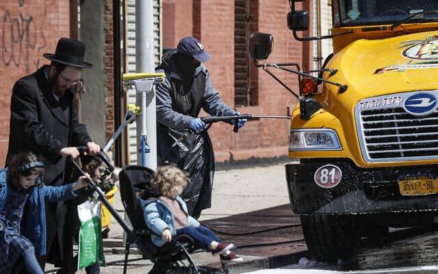 עובד מכוסה בציוד מגן שוטף אוטובוס הסעות של בית ספר המשמש את הקהילה החרדית היהודיות בברוקלין, ניו יורק, 27 במארס, 2020 (צילום: AP\ ג'ון מינצ'ילו)