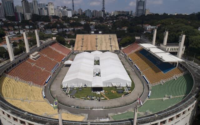 עובדים מקימים בית חולים שדה ארעי לטיפול בחולי קוביד-19 באצטדיון פקאמבו בסאו פאולו, ברזיל, 30 במרץ 2020 (צילום: AP/אנדרה פנר)