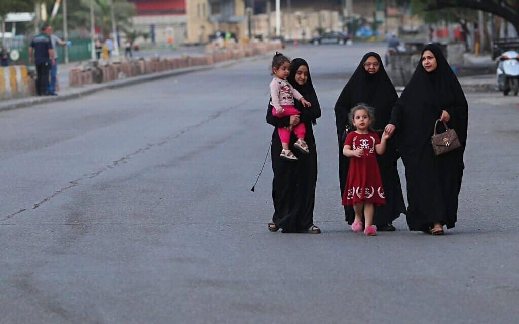 מגפת הקורונה בעיראק: קבוצת נשים וילדות ברחוב כמעט-שומם בבגדד (צילום: AP Photo/Hadi Mizban)