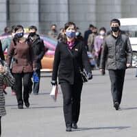 הולכי רגל עוטים מסכות על פניהם בפיונגיאנג, 1 באפריל 2020 (צילום: Cha Song Ho, AP)
