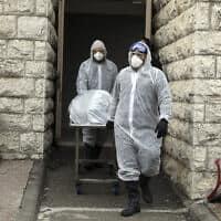 אנשי חברה קדישא מפנים גופה של חולה שמת מקורונה בירושלים, 1 באפריל 2020 (צילום: Mahmoud Illean, AP)