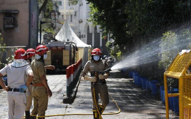 לוחמי אש בדלהי מחטאים את אזור ניזאמודין, שבו התגלה אחוז גבוה של נדבקים בווירוס הקורונה, אחרי שהשתתפו בארוע טאבליגי ג'מעעת (צילום: AP Photo/Manish Swarup)