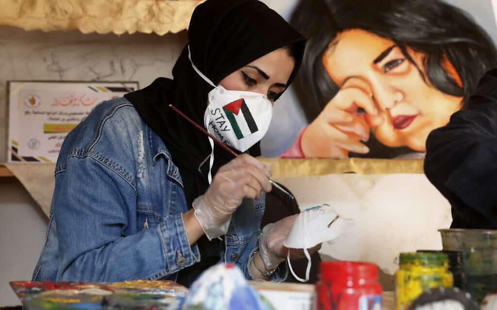התפרצות הקורונה בעזה: אמנית מקומית מקשטת מסכות כדי לעודד אנשים לחבוש אותן, אפריל 2020 (צילום: AP Photo/Adel Hana)