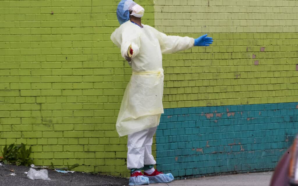 בוקר טוב עולם: עובד בית חולים יוצא מחדר המיון כדי לשאוף אוויר, ניו יורק סיטי, 4 באפריל 2020 (צילום: AP Photo/Mary Altaffer)