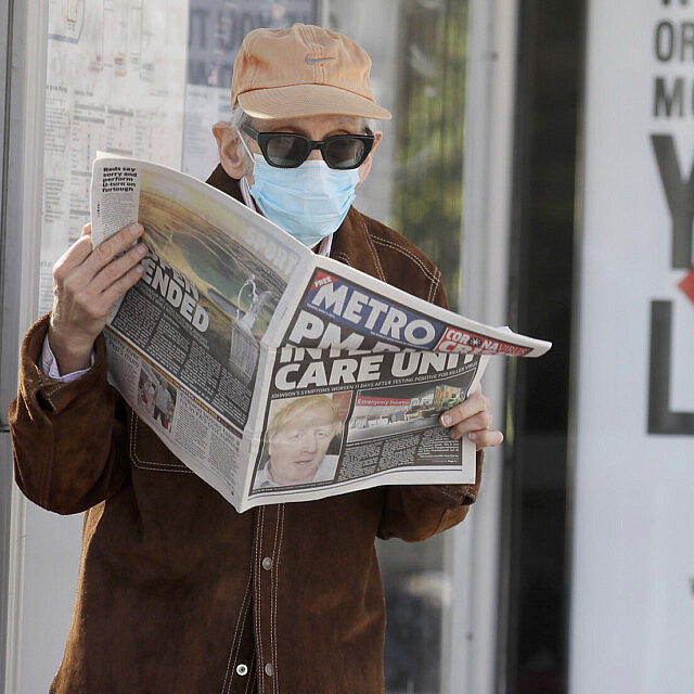 אדם בלונדון קורא עיתון שעל השער שלו הכותרת: ראש הממשלה בטיפול נמרץ. 7 באפריל 2020 (צילום: AP Photo/Kirsty Wigglesworth)