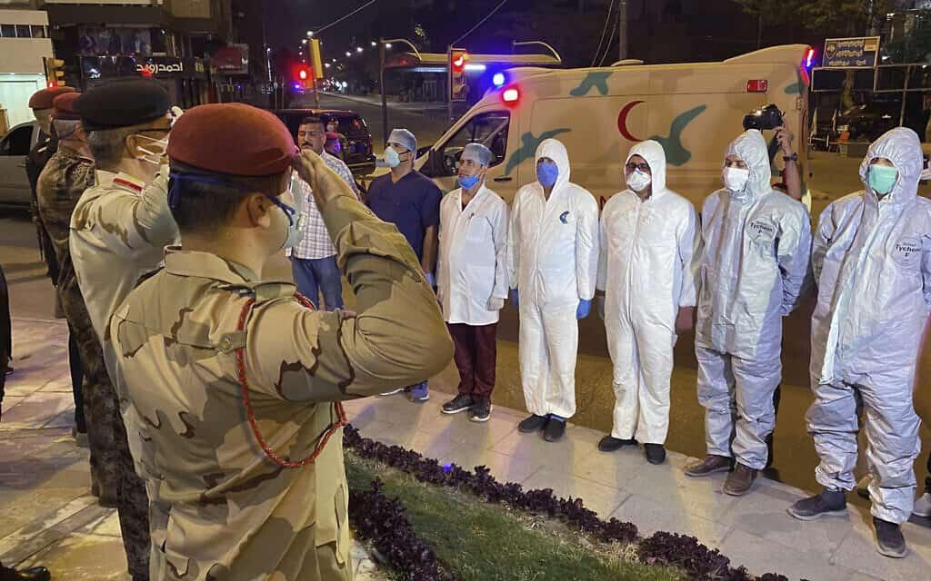 התפרצות הקורונה בעיראק: קצינים מצדיעים לעובדי מערכת הבריאות, אפריל 2020 (צילום: AP Photo/Hadi Mizban)