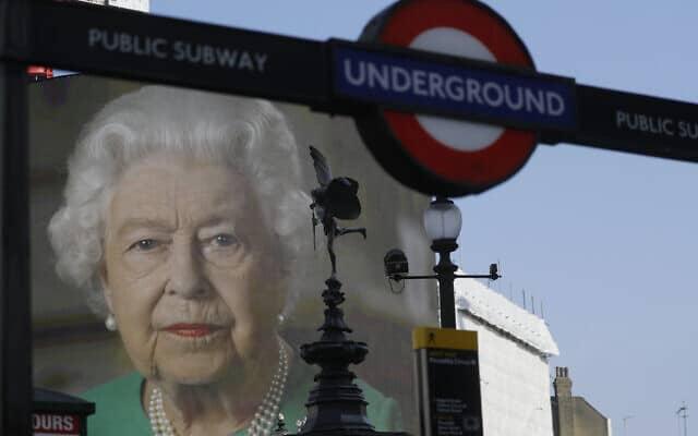 קטעים מהנאום ההיסטורי של אליזבת מלכת בריטניה מוקרנים שוב ושוב על המסך הגדול בכיכר פיקדילי בלונדון (צילום: AP Photo/Kirsty Wigglesworth)
