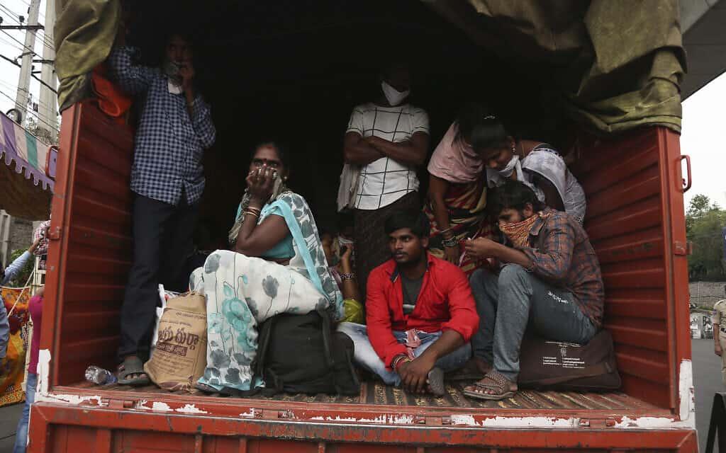 עובדים הודים שנעצרו בדרכם לביתם והועלו על משאית של הממשלה – בדרך למחנה הסגר. 14 באפריל 2020 (צילום: AP Photo/Mahesh Kumar A)