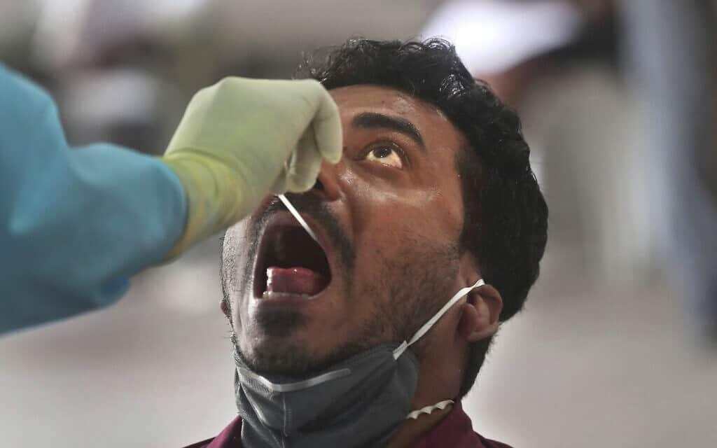 רופא מבצע בדיקת קורונה במומביי, הודו, ב-16 באפריל 2020 (צילום: AP Photo/Rafiq Maqbool)