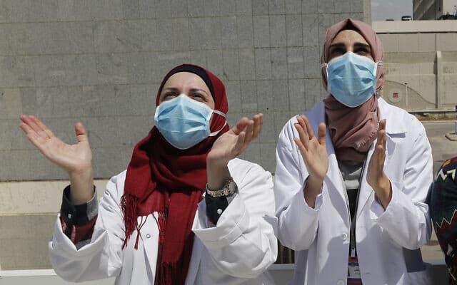 עידן הקורונה: אחיות בלבנון מריעות למוזיקאים שבאו לשמח אותן ממרפסת סמוכה, אפריל 2020 (צילום: AP Photo/Hussein Malla)