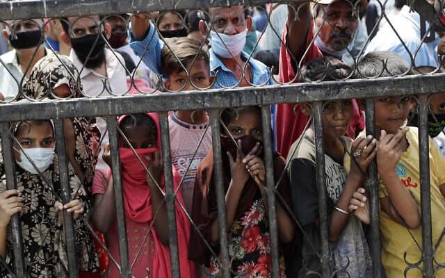 ילדים בשכונת סלאמס ממתינים לחלוקת אוכל, במומביי, הודו. 18 באפריל 2020 (צילום: AP Photo/Rajanish Kakade)