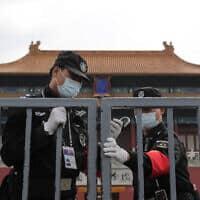 עידן הקורונה: שוטרים בעיר האסורה בסין (צילום: AP Photo/Andy Wong)