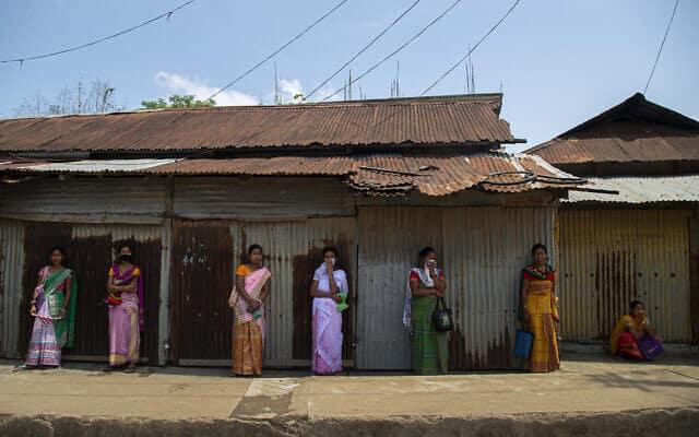 נשים ממתינות מחוץ לחנות מכולת בכפר גרנגירי, מערבית לגוהאטי בהודו. 20 באפריל 2020 (צילום: AP Photo/Anupam Nath)