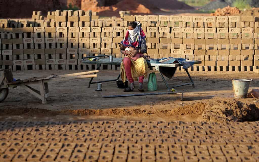 ילדה הודית מחכה לאמה מחוץ לכותלי מפעל בהודו, שהורשה לחזור לעבודה, ב-22 באפריל 2020 (צילום: AP Photo/ Channi Anand)