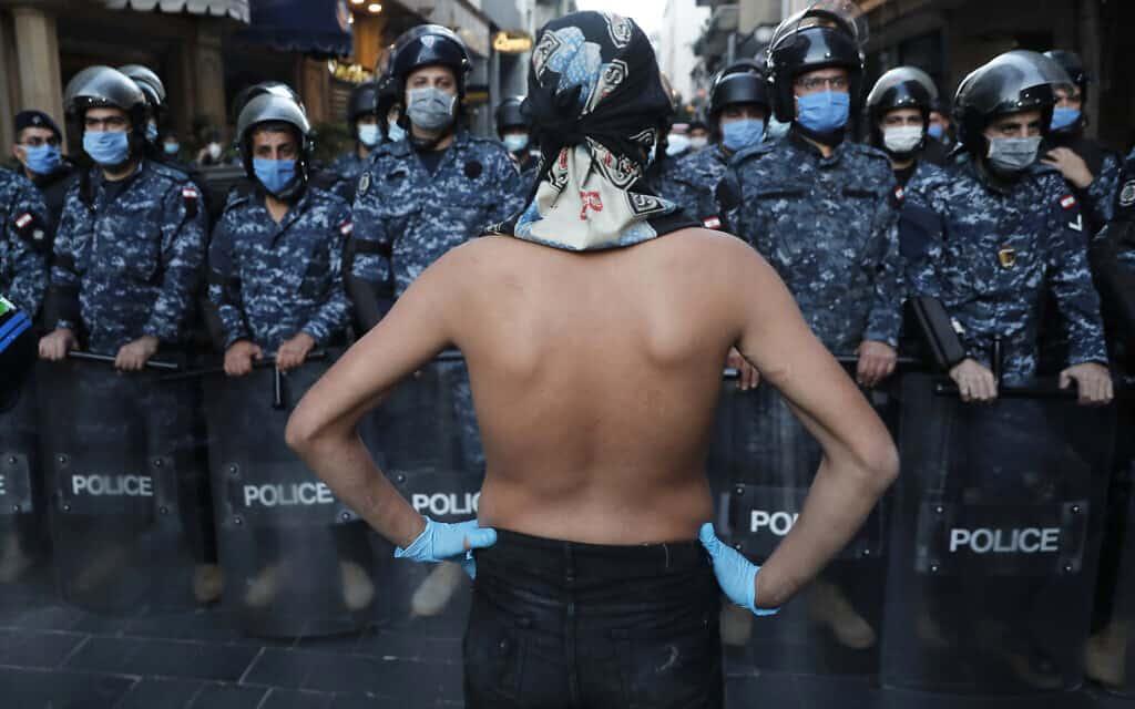 עידן הקורונה: מפגין לבנוני ניצב מול שוטרים בביירות, 23 באפריל 202 (צילום: AP Photo/Hussein Malla)