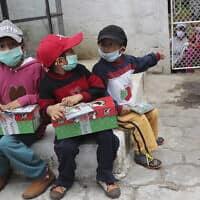 משבר הקורונה באקוודור: ילדים אוחזים חבילות שי שקיבלו מארגוני סיוע (צילום: AP Photo/Dolores Ochoa)