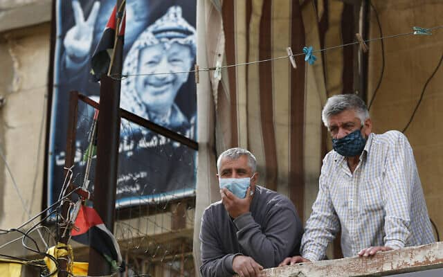 התנתקו מהחדשות! גברים פלסטינים צופים מהמרפסת בביקור שר הבריאות הלבנוני במחנה פליטים (צילום: AP Photo/Hussein Malla)