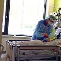 אחות בבית חולים בדיסלדורף, גרמניה, מטפלת בחולה קורונה. 29 באפריל 2020 (צילום: AP Photo/Matthias Schrader)