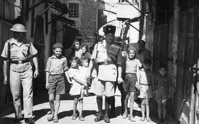 קצין משטרה בריטי מסייע לילדים יהודיים לחצות בבטחה את רחובות ירושלים, אוקטובר 1938 (צילום: AP Photo/James Mills)