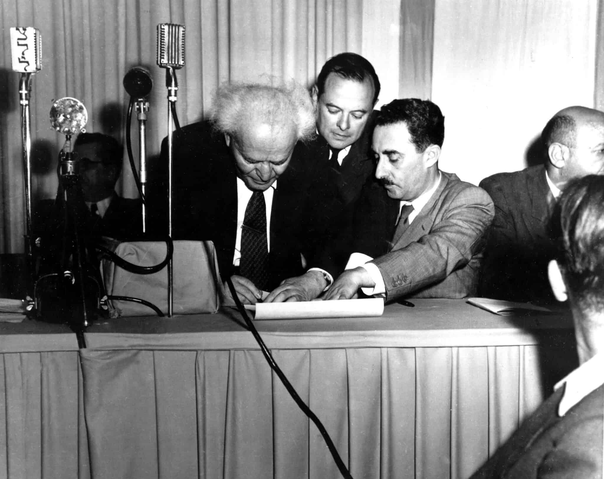 דוד בן גוריון חותם על מגילת העצמאות ב-14 במאי 1948. מימינו, משה שרת (צילום: AP Photo)