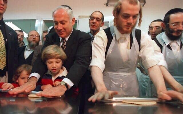 בנימין נתניהו רותם את ילדיו יאיר ואבנר לקמפיין בחירות 1999, ומסייר במפעל לייצור מצות בירושלים לקראת פסח (צילום: AP Photo/Eyal Warshavsky)
