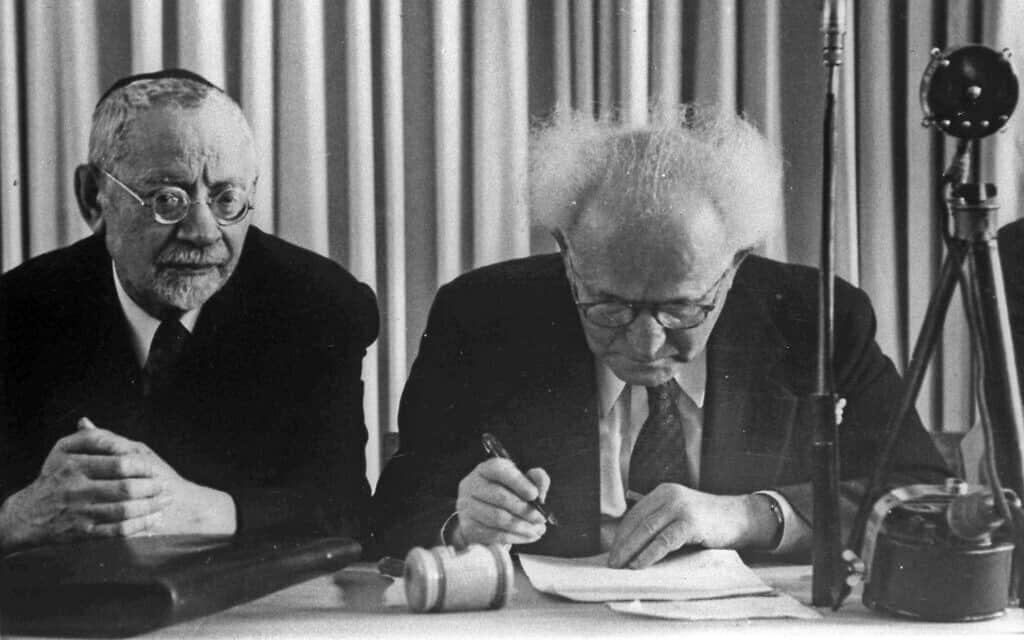 דוד בן גוריון חותם על מגילת העצמאות, משמאלו הרב יהודה לייב הכהן. 14 במאי 1948 (צילום: האנס פין/לע״מ)