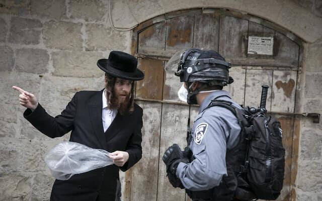 שוטר בשכונת מאה שערים, דורש ממתפלל לחזור לביתו. 31 במרץ 2020 (צילום: Olivier Fitoussi/Flash90)