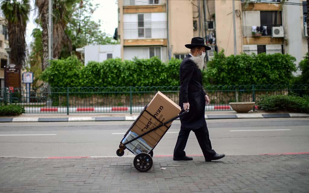 תושב חרדי בבני ברק צועד הביתה בעיר הריקה. 1 באפריל 2020 (צילום: תומר נויברג/פלאש90)