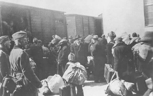 שוטרים בולגרים מפקחים על גירושם של יהודי מקדוניה למחנות המוות הגרמניים במרץ 1943 בסקופיה, שהייתה תחת כיבוש בולגרי (צילום: איי-פי/מוזיאון ארצות הברית לזכר השואה, באדיבות המוזיאון להיסטוריה יהודית בבלגרד)