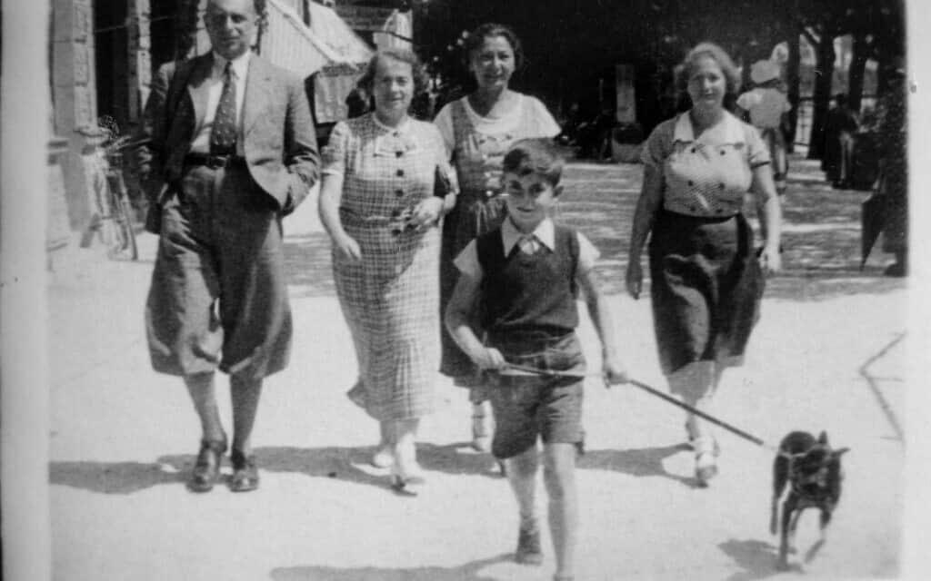 """אוטו אולמן מוביל כלב ברחוב בווינה. מאחוריו, משמאל, יוזף """"פפי"""" אולמן, אליזה אולמן, אישה שזהותה אינה ידועה וגרתה, דודתו של אוטו מצד אמו (צילום: אליזבת אוסברינק)"""