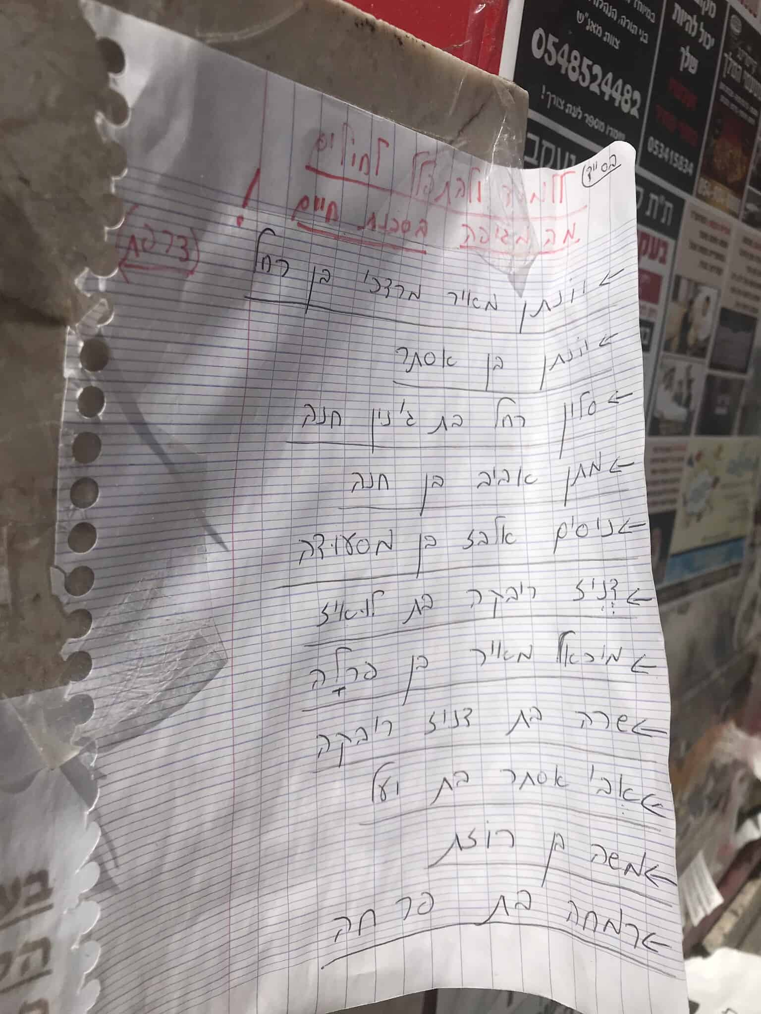 """דף שעליו שורבטה בעיפרון אדום תחינה """"ללמוד ולהתפלל לחולים מהמגיפה בסכנת חיים"""" ותחתיה שמות רבים של חולים בני העיר בני ברק (צילום: אמיר בן-דוד)"""