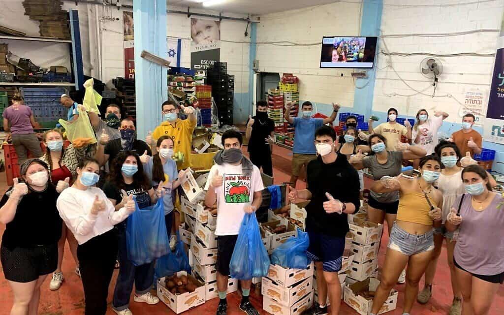 תלמידי מחזור האביב של Year Course חובשים מסכות כשהם מבצעים עבודת התנדבות בקהילה (צילום: באדיבות Year Course)