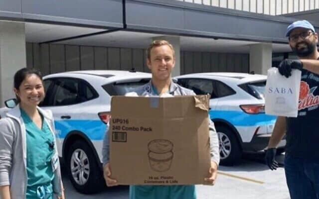 """אלון שעיה מביא חומוס ופיתות לעובדי רפואה במסגרת @noladocproject (צילום: """"סבא"""", פייסבוק)"""