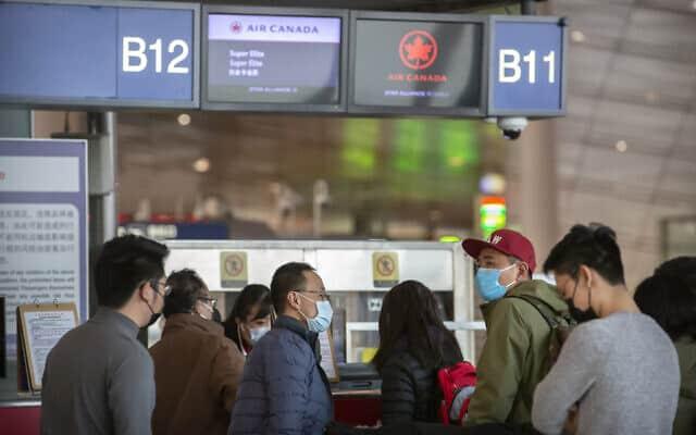נוסעים עוטים מסכות בדלפקי הצ׳ק אין בנמל התעופה בבייג'ינג (צילום: AP Photo/Mark Schiefelbein)