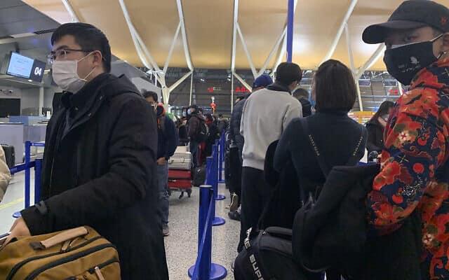נוסעים עוטים מסכות בדלפקי הצ׳ק אין בנמל התעופה בשנגחאי (צילום: AP Photo/Erika Kinetz)