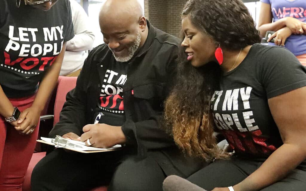former felon Desmond Meade and president of the Florida Rights Restoration Coalition, left, fills out a voter registration form (צילום: AP Photo/John Raoux, File)