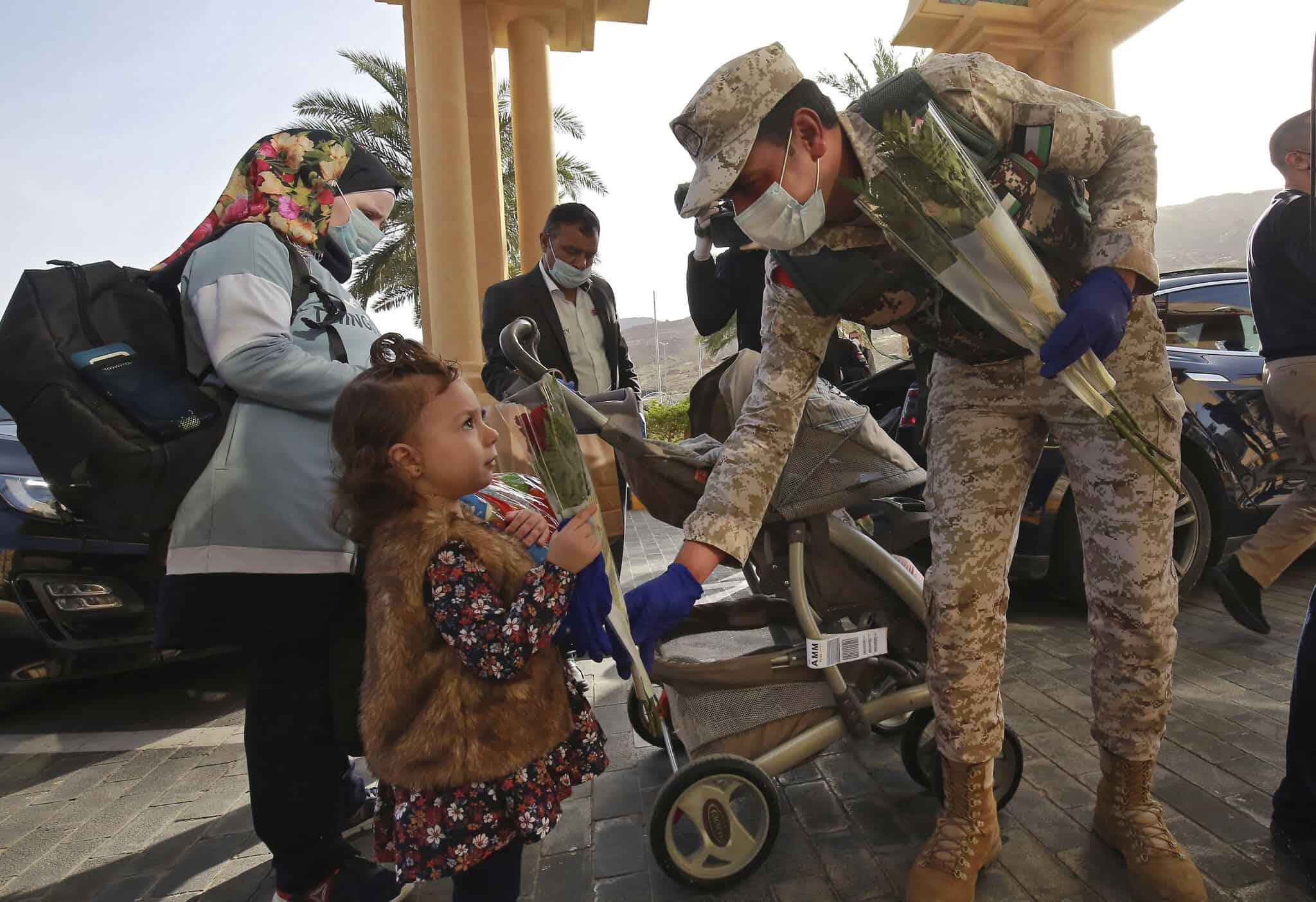חיילים ירדנים מחלקים פרחים לתושבים שהיו נתונים לסגר ממושך בצד הירדני של ים המלח, 30 במרץ 2020 (צילום: halil Mazraawi/Pool via AP)