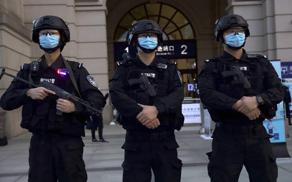 שוטרים במסכות עומדים מחוץ לתחנת הרכבת בווהאן. אפריל 2020 (צילום: AP Photo/Ng Han Guan)