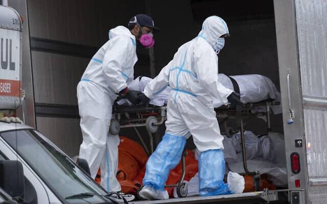 עובדים ממוגנים מעבירים גופות למשאית קירור ברובע ברוקלין שבניו יורק, 29 באפריל 2020 (צילום: Craig Ruttle, AP)