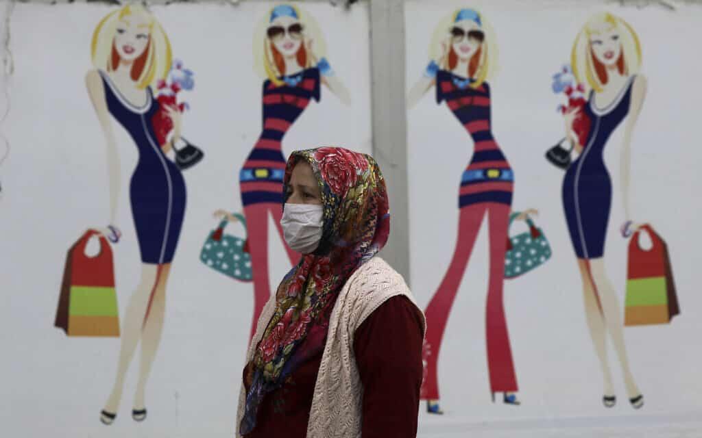 אישה חולפת ליד חנות בגדים סגורה בטורקיה, השבוע (צילום: AP Photo/Ali Unal)