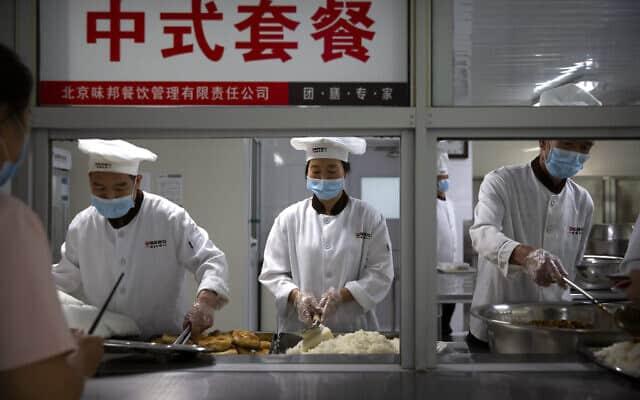 עובדים לובשים מסכות פנים וכפפות מגישים ארוחת צהריים. מאי 2020 (צילום: AP Photo/Mark Schiefelbein)