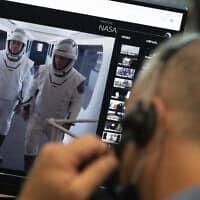 """האסטרונאוטים של נאס""""א, שאמורים לטוס לחלל במשימה של חברת SpaceX, על צג מוניטור במרכז החלל קנדי בפלורידה, 23 במאי 2020 (צילום: Joel Kowsky/NASA via AP)"""